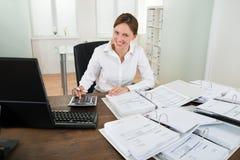 Geschäftsfrau Calculating Financial Data am Schreibtisch Stockbilder