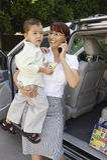 Geschäftsfrau Carrying Son While beim Anruf Stockfotos