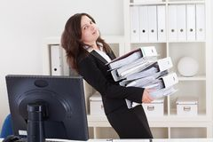 Geschäftsfrau-Carrying Stack Of-Ordner Stockbilder
