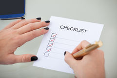 Geschäftsfrau-With Checklist At-Schreibtisch lizenzfreie stockfotos