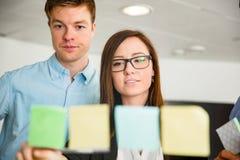 Geschäftsfrau And Colleague Looking an den Anmerkungen gehaftet auf Glas lizenzfreie stockbilder