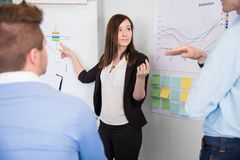 Geschäftsfrau Communicating With Colleague beim Zeigen bei Cha stockbild
