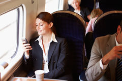 Geschäftsfrau Commuting To Work auf Zug unter Verwendung des Handys Stockfotos