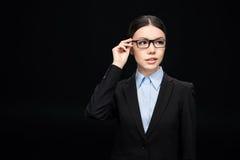 Geschäftsfrau in den Brillen und in schwarzem Anzug lokalisiert auf Schwarzem Stockfoto