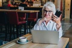 Geschäftsfrau in den Gläsern sitzt bei Tisch vor Laptop Stockfotos