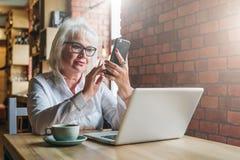 Geschäftsfrau in den Gläsern sitzt bei Tisch vor Laptop und benutzt Smartphone Ausbildung für Erwachsene freiberufler Lizenzfreies Stockfoto