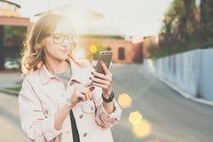 Geschäftsfrau in den Gläsern steht auf einer Stadtstraße und benutzt einen Smartphone Hintergrundbeleuchtung Blogging Hippie-Mädc Lizenzfreie Stockfotografie