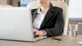 Geschäftsfrau in den Klagen, welche die Audio- und Mikrofonschnüre im Laptop verstopfen stock video