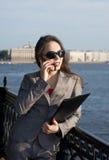 Geschäftsfrau in den Sonnenbrillen sprechend am Telefon Lizenzfreie Stockfotografie