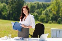 Geschäftsfrau in den sonnigen Naturbüro-Einflussfaltblättern Stockfotos