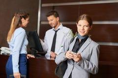 Geschäftsfrau an der Abfertigung im Hotel lizenzfreies stockbild