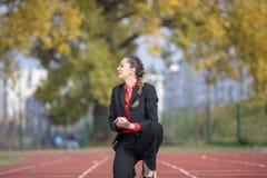 Geschäftsfrau in der Anfangsposition bereit, auf laufender Bahn der Leichtathletik zu laufen und zu sprinten Lizenzfreie Stockfotografie