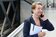 Geschäftsfrau in der Flughafen- oder Zug-U-Bahnmetrostation, die einen Telefonanruf mit Smartphone macht Lizenzfreie Stockfotografie