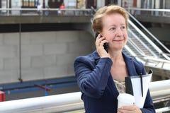 Geschäftsfrau in der Flughafen- oder Zug-U-Bahnmetrostation, die einen Telefonanruf mit Smartphone macht Stockfoto