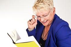 Geschäftsfrau in der Jacke mit Gläsern ein Buch lesend Lizenzfreie Stockfotos
