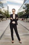 Geschäftsfrau in der Klage, die draußen an der Straße steht Lizenzfreies Stockfoto