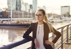 Geschäftsfrau in der Klage, die nahe dem Flussstadthintergrund steht Stockbild