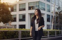 Geschäftsfrau in der Klage draußen gehend Stockbild