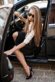 Geschäftsfrau in der weißen Bluse und schwarzen im Rock, die in einem blac sitzt Stockfotografie