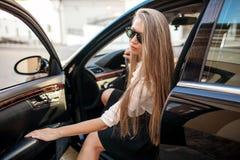 Geschäftsfrau in der weißen Bluse und schwarzen im Rock, die in einem blac sitzt Stockfotos