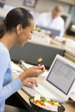 Geschäftsfrau in der Zelle mit Laptop Salat essend Lizenzfreies Stockfoto