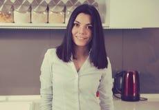Geschäftsfrau in der zufälligen Kamera betrachtenden und bei der Stellung lächelnden Kleidung in einer Küche stockbild