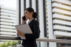 Geschäftsfrau, die über dem intelligenten Telefon bespricht das Projekt spricht Stockfotografie