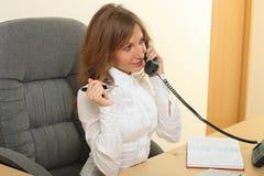 Geschäftsfrau, die über dem Telefon speeking ist Lizenzfreies Stockfoto