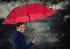 Geschäftsfrau, die über Schulter mit Regenschirm gegen regnerischen Himmel schaut Stockfotografie