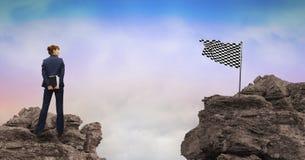 Geschäftsfrau, die überprüfte Flagge auf Felsen betrachtet Stockbild