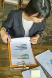 Geschäftsfrau, die Überprüfung von Daten tut stockfotografie