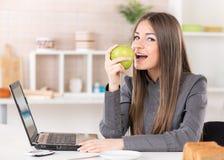 Geschäftsfrau, die Apfel isst Lizenzfreie Stockbilder
