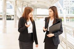Geschäftsfrau, die außerhalb des Büros geht und miteinander spricht stockfoto