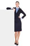 Geschäftsfrau, die auf Anschlagtafel sich lehnt lizenzfreie stockbilder