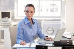 Geschäftsfrau, die auf Arbeit sich konzentriert Lizenzfreies Stockbild