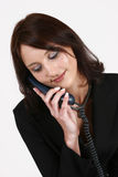 Geschäftsfrau, die auf aufrufendes Programm am Telefon hört Lizenzfreie Stockbilder