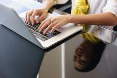 Geschäftsfrau, die auf Büro-Laptop-Computer lächelt und schreibt Lizenzfreies Stockfoto