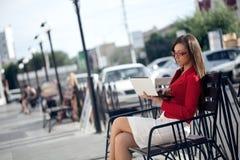 Geschäftsfrau, die auf Bank sitzt Lizenzfreies Stockbild