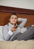 Geschäftsfrau, die auf Bett und aufpassendes Fernsehen legt Stockbild