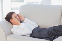 Geschäftsfrau, die auf Couch mit Kopfschmerzen liegt stockbild