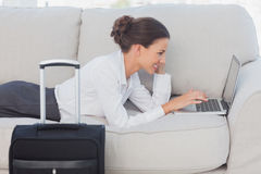 Geschäftsfrau, die auf Couch mit Laptop und Koffer liegt Lizenzfreie Stockfotografie