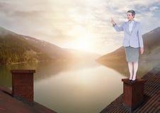 Geschäftsfrau, die auf Dächern mit Kamin und Seeberglandschaft steht Lizenzfreie Stockbilder