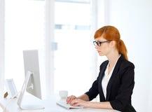 Geschäftsfrau, die auf dem Computer schreibt Stockfotografie