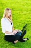 Geschäftsfrau, die auf dem Gras sitzt Stockfotografie