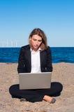 Geschäftsfrau, die auf dem Sand mit Laptop sitzt Stockbild