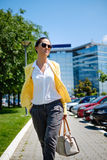 Geschäftsfrau, die auf den Bürgersteig geht Stockbild
