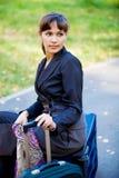 Geschäftsfrau, die auf einem Gepäck sitzt. stockbilder