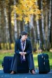 Geschäftsfrau, die auf einem Gepäck sitzt stockfotografie