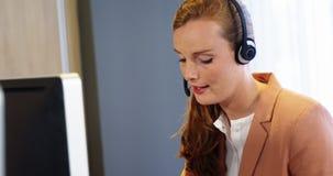 Geschäftsfrau, die auf einem Kopfhörer am Schreibtisch spricht stock video