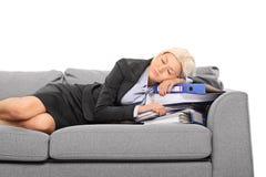 Geschäftsfrau, die auf einem Stapel von Dokumenten schläft Lizenzfreie Stockbilder